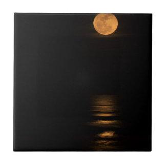 golden full moon over ocean tile