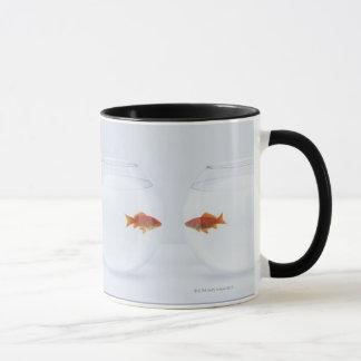 Goldfish in separate fishbowls looking face to mug