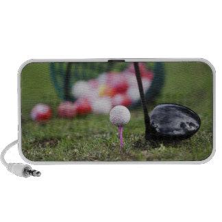Golf ball on tee beside golf club speakers
