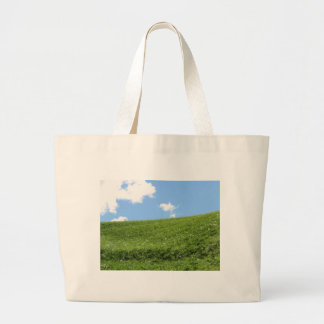Grassy field at the rolling hill against the sky large tote bag