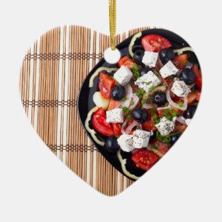 Greek vegetarian salad of tomatoes, cucumbers, oni ceramic heart decoration