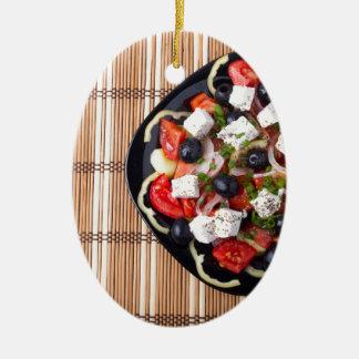 Greek vegetarian salad of tomatoes, cucumbers, oni ceramic oval decoration