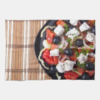 Greek vegetarian salad of tomatoes, cucumbers, oni kitchen towel
