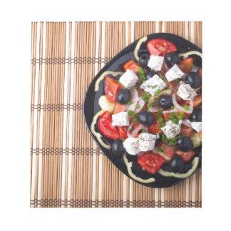 Greek vegetarian salad of tomatoes, cucumbers, oni notepads