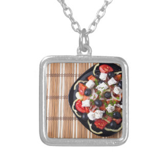 Greek vegetarian salad of tomatoes, cucumbers, oni silver plated necklace