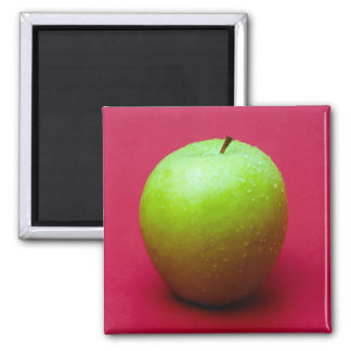 Green apple on red background square magnet