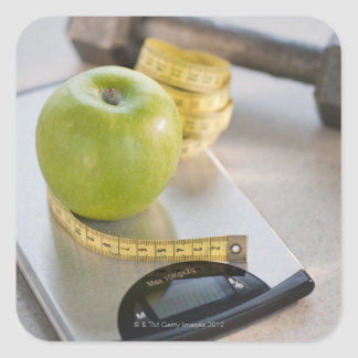 Green apple on weight scale, tape measure and stickers