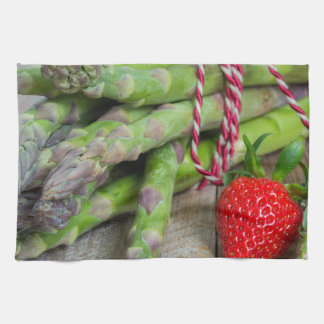 Green asparagus with strawberries on wooden tea towel