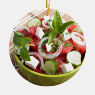 Green bowl with tasty and wholesome vegetarian round ceramic decoration