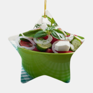 Green bowl with vegetable salad on tablecloth ceramic ornament