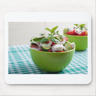 Green bowl with vegetable salad on tablecloth mouse pad