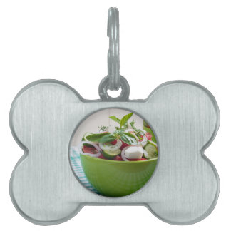 Green bowl with vegetable salad on tablecloth pet tag