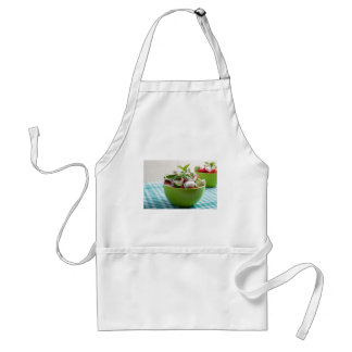 Green bowl with vegetable salad on tablecloth standard apron