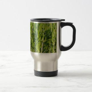 Green corn plants are growing in summer travel mug
