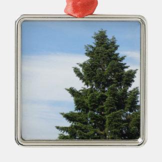 Green fir tree against a clear sky metal ornament