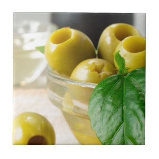 Green marinated olives pitted adorned with green small square tile