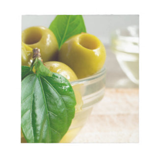 Green marinated olives pitted in a glass cup notepad