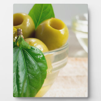 Green marinated olives pitted in a glass cup plaque