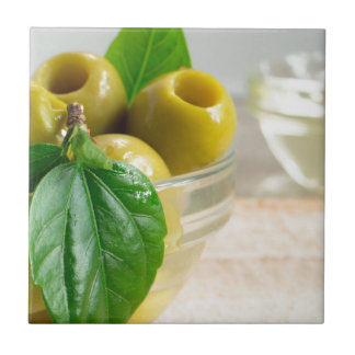 Green marinated olives pitted in a glass cup small square tile