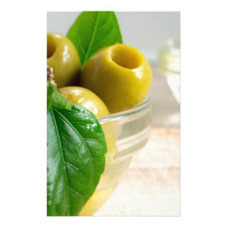Green marinated olives pitted in a glass cup stationery