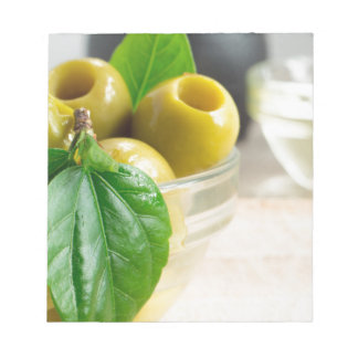 Green pickled pitted olives closeup notepad