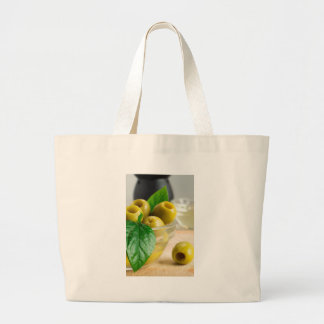 Green pickled pitted olives in a glass bowl large tote bag
