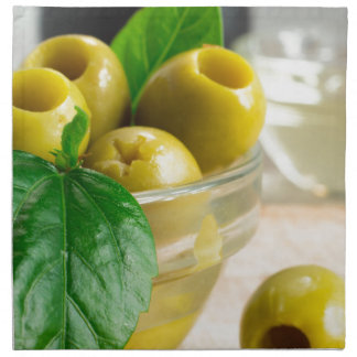 Green pickled pitted olives in a glass bowl napkin