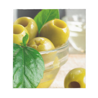 Green pickled pitted olives in a glass bowl notepad