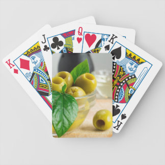 Green pickled pitted olives in a glass bowl poker deck