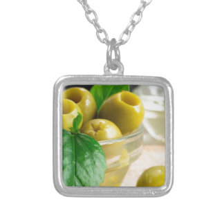 Green pickled pitted olives in a glass bowl silver plated necklace