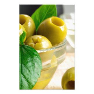 Green pickled pitted olives in a glass bowl stationery