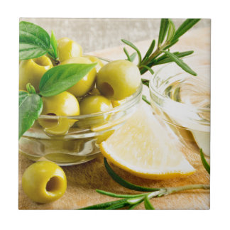 Green pitted olives decorated with herbs small square tile