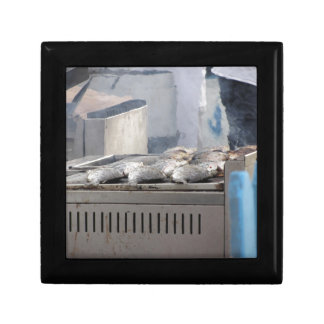 Grilling fish outdoors with smoke emerging gift box