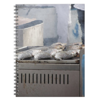 Grilling fish outdoors with smoke emerging notebook