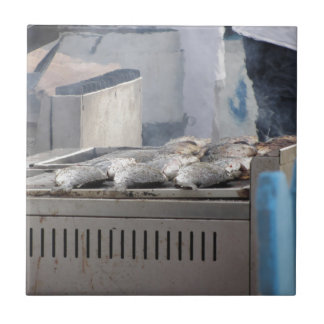 Grilling fish outdoors with smoke emerging tile