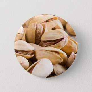 Group of salted pistachios in a small wooden box 6 cm round badge