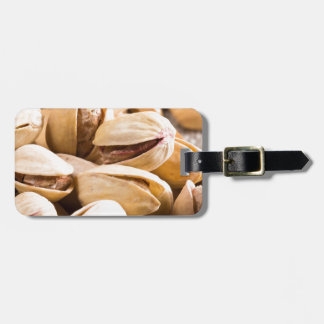 Group of salted pistachios in a small wooden box luggage tag