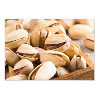 Group of salted pistachios in a small wooden box photo print