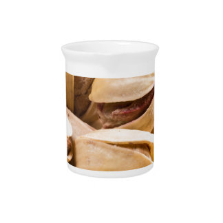 Group of salted pistachios in a small wooden box pitcher