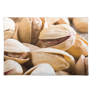 Group of salted pistachios in a small wooden box placemat