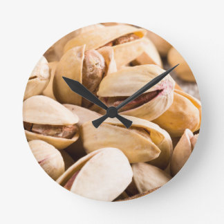 Group of salted pistachios in a small wooden box round clock