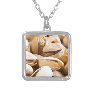 Group of salted pistachios in a small wooden box silver plated necklace