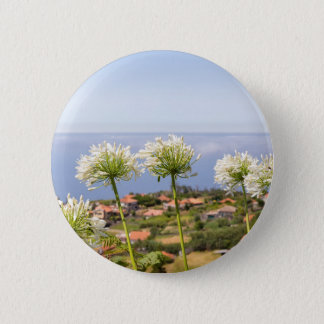 Group of white agapanthus near village and sea 6 cm round badge