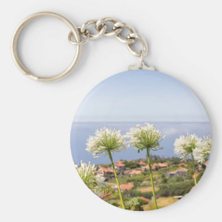 Group of white agapanthus near village and sea basic round button key ring