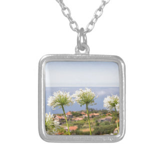 Group of white agapanthus near village and sea silver plated necklace
