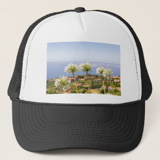 Group of white agapanthus near village and sea trucker hat