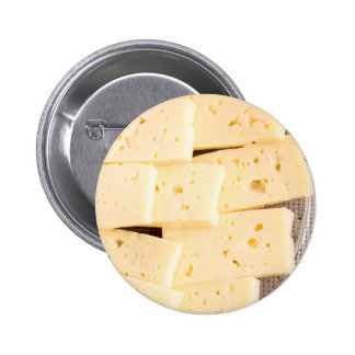 Group slices dry hard yellow cheese on a plate 6 cm round badge