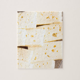 Group slices dry hard yellow cheese on a plate jigsaw puzzle