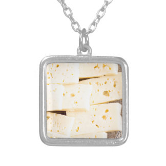 Group slices dry hard yellow cheese on a plate silver plated necklace