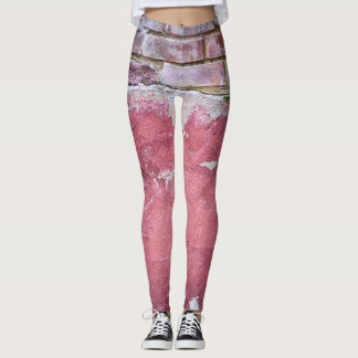 Grunge red wall with broken plaster close up leggings